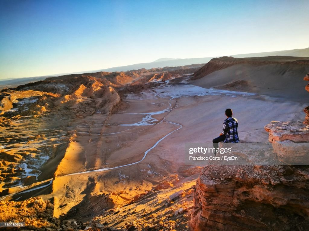 Man Sitting On Rock Formation At Valle De La Luna : Stock Photo