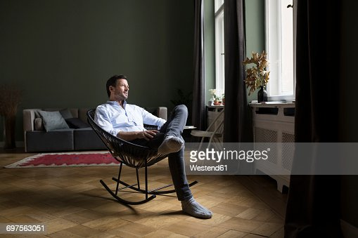 Man sitting on rocking chair in his living room looking through window