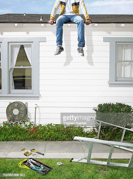 Man sitting on roof of house, ladder on lawn