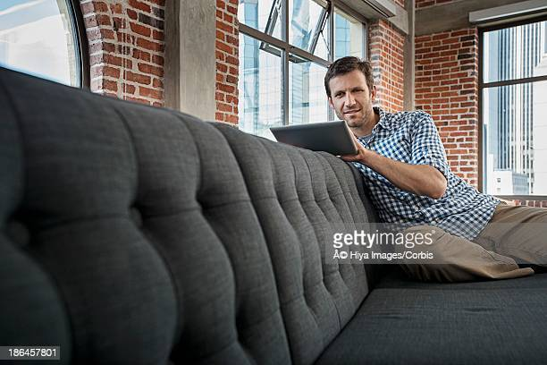 Man sitting on sofa and using digital tablet