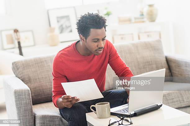 Man sitting on sofa and using laptop