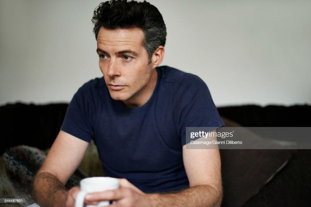 Man sitting on sofa holding mug looking sad : Stock Photo