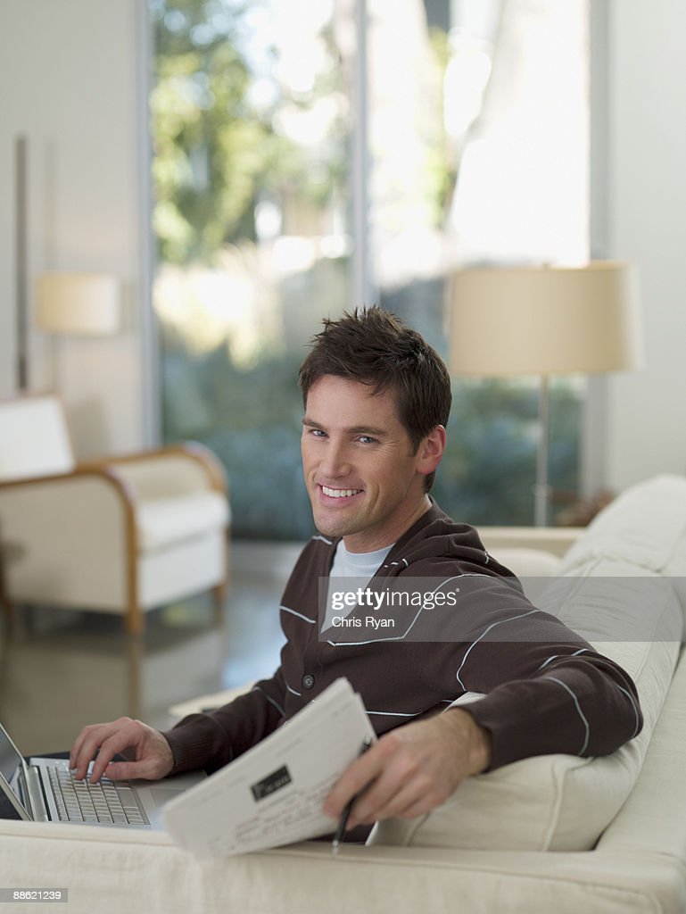 Man sitting on sofa holding papers : Stock Photo