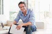 Man sitting on sofa holding paperwork