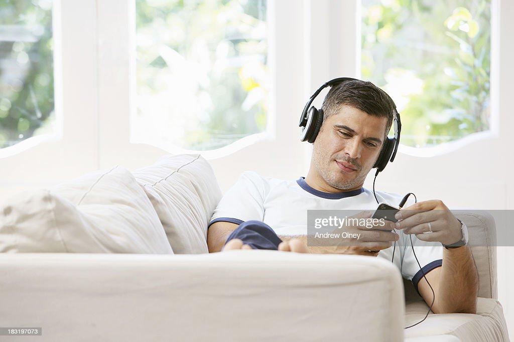 man sitting on sofa listening with headphones : Stock Photo