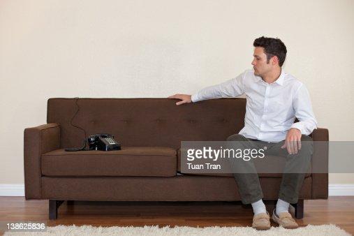 Man sitting on sofa looking at phone : Stock Photo