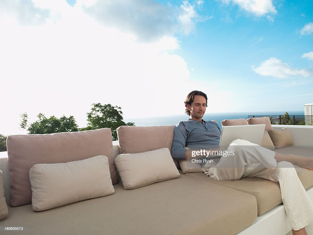 Man sitting on sofa outdoors with laptop and sky : Stock Photo