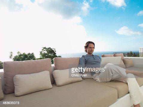 Hombre sentado en el sofá con portátil y Cielo al aire libre