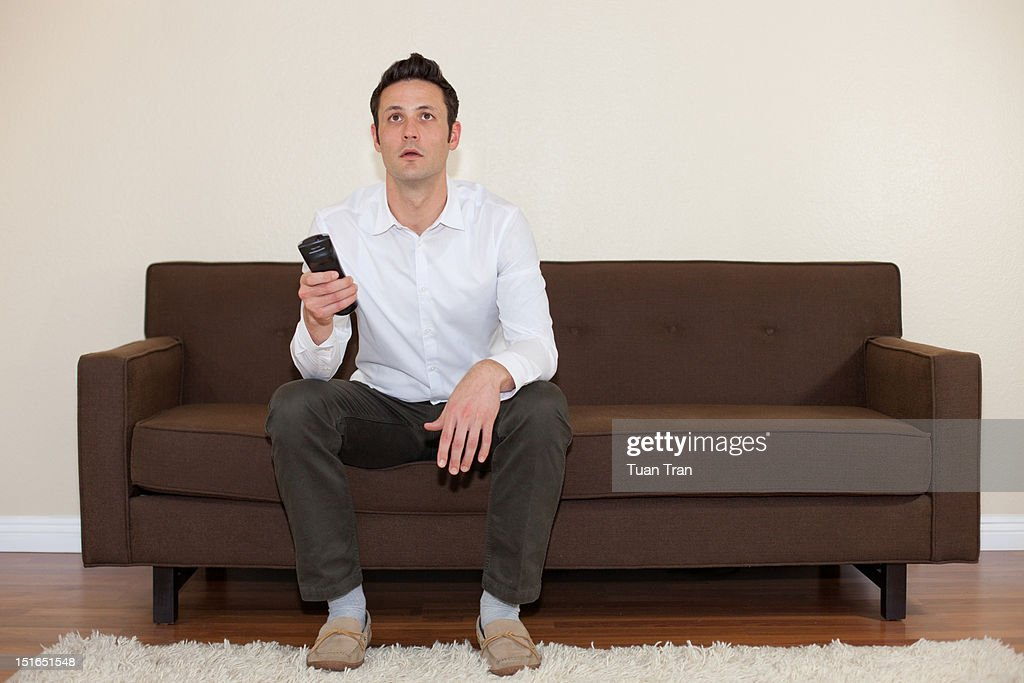 man sitting on sofa stock photo getty images. Black Bedroom Furniture Sets. Home Design Ideas