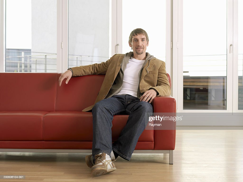 Man sitting on sofa, portrait : Stock Photo