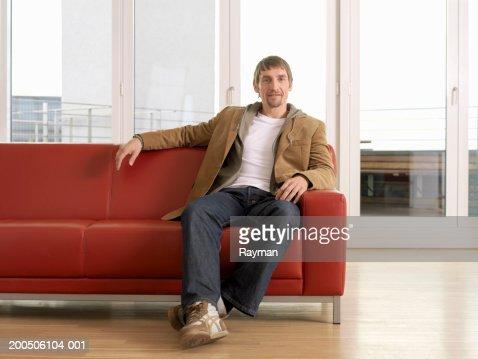 Man sitting on sofa, portrait : Stock Photo