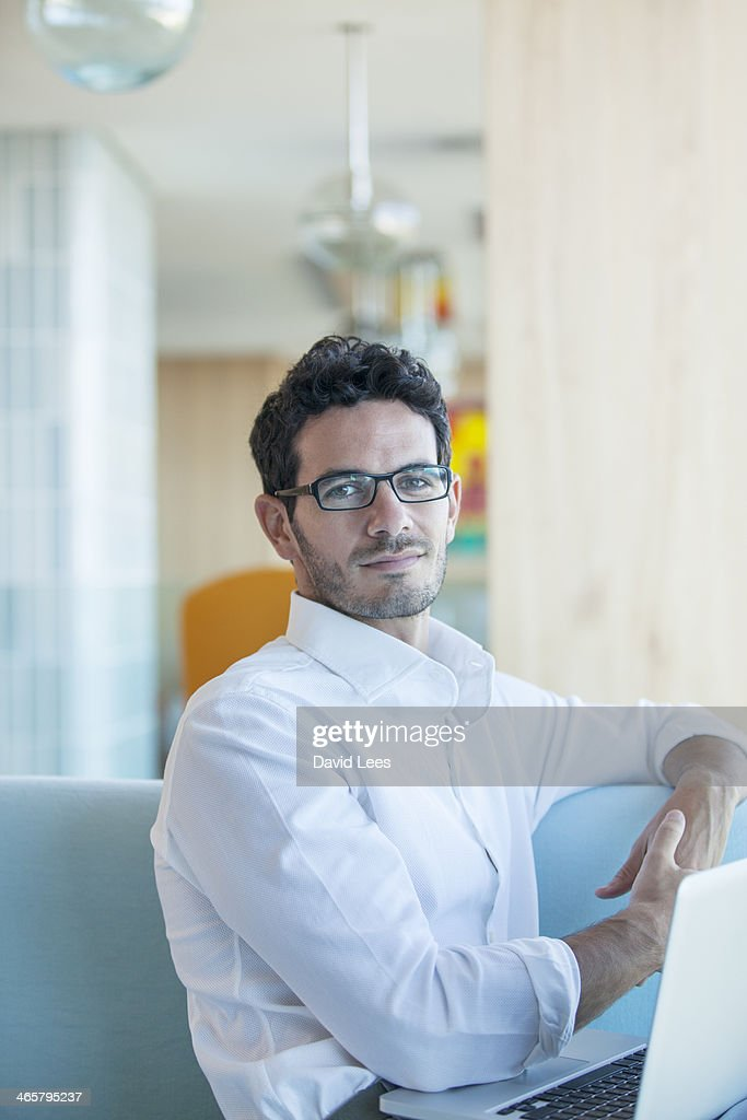 Man sitting on sofa using laptop : Stock Photo