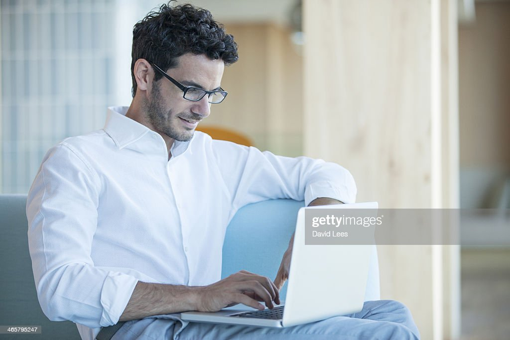 Man sitting on sofa using laptop : Stock Photo