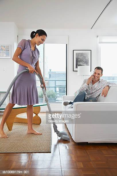 Man sitting on sofa using mobile phone, woman vacuuming floor
