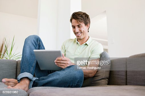 Man sitting on sofa using tablet pc : ストックフォト
