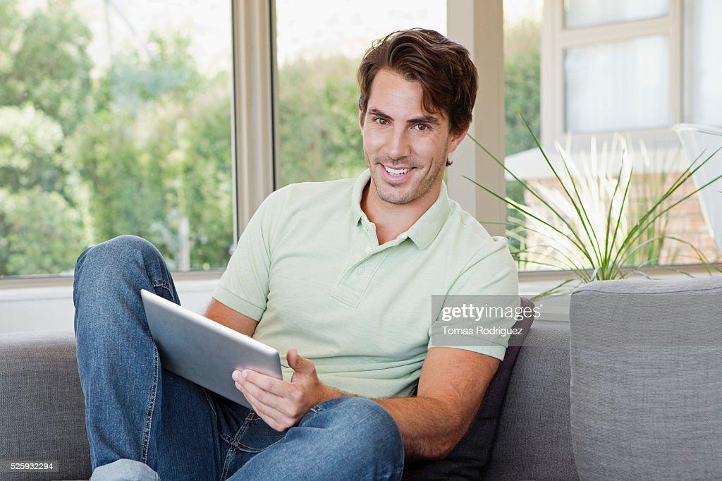 Man sitting on sofa using tablet pc : Foto stock
