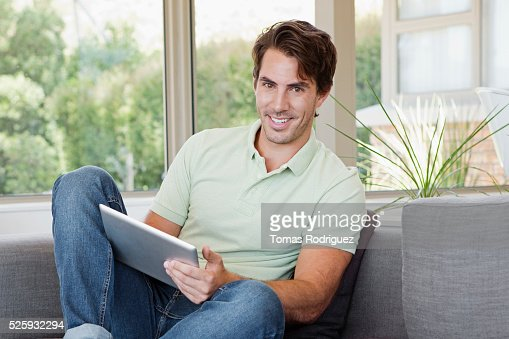Man sitting on sofa using tablet pc : Stock Photo