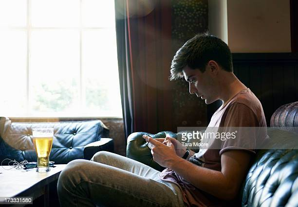 man sitting on sofa with beer texting