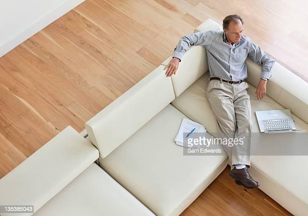 男性のソファーに座ってラップトップと書類