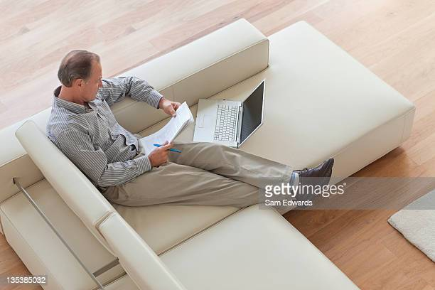 Man sitting on sofa with laptop looking at paperwork