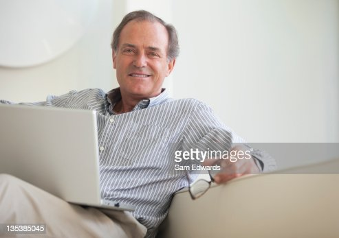 Man sitting on sofa with laptop : Stock Photo