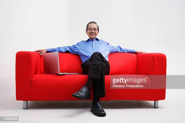 Man sitting on sofa with laptop