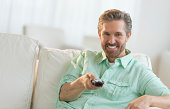 Portrait of happy mature man sitting on sofa with remote control at home