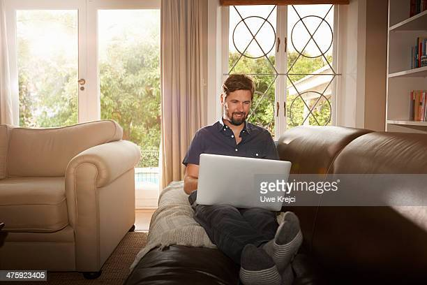 Man sitting on sofa working with laptop