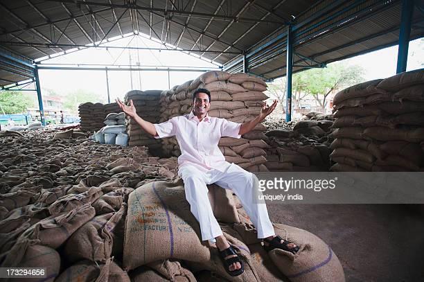 Man sitting on stack of wheat sacks in a warehouse, Anaj Mandi, Sohna, Gurgaon, Haryana, India