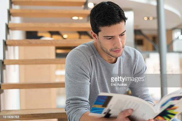 Man sitting on stairs and reading a magazine