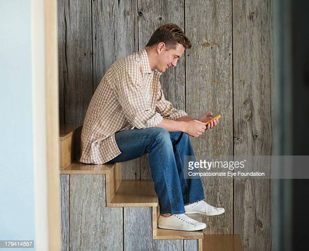 Man sitting on stairs texting on mobile phone