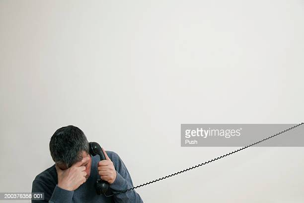 Man sitting on stairs using telephone, hand to forehead