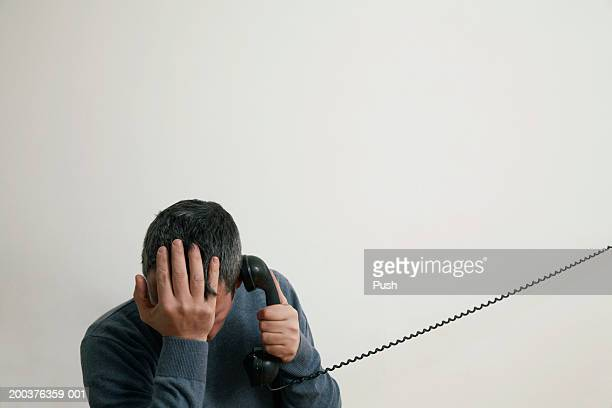 Man sitting on stairs using telephone, hand to head