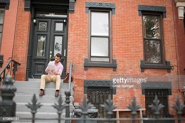 Man sitting on step using digital tablet