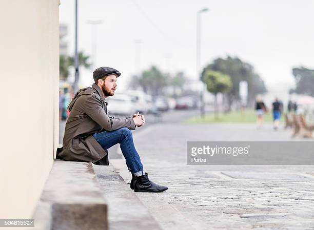 Man sitting on steps at sidewalk