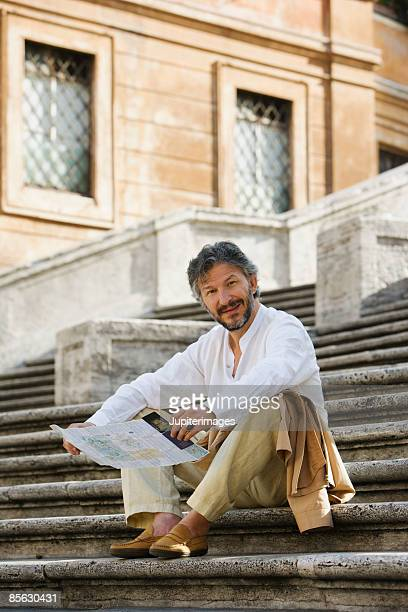 Man sitting on stone stairs with map