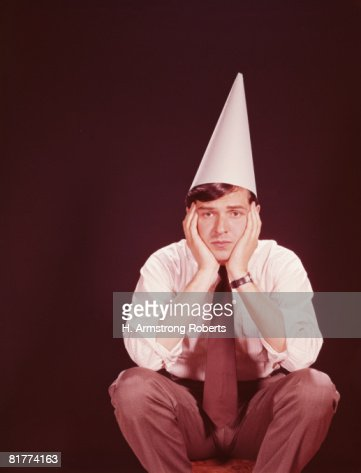 Man sitting on stool, wearing dunce's hat. (Photo by H. Armstrong Roberts/Retrofile/Getty Images) : Stock Photo