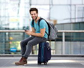 Portrait of a young man sitting on suitcase and sending text message