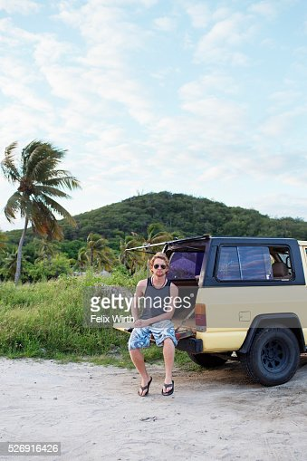 Man sitting on tailgate of truck : Stock Photo