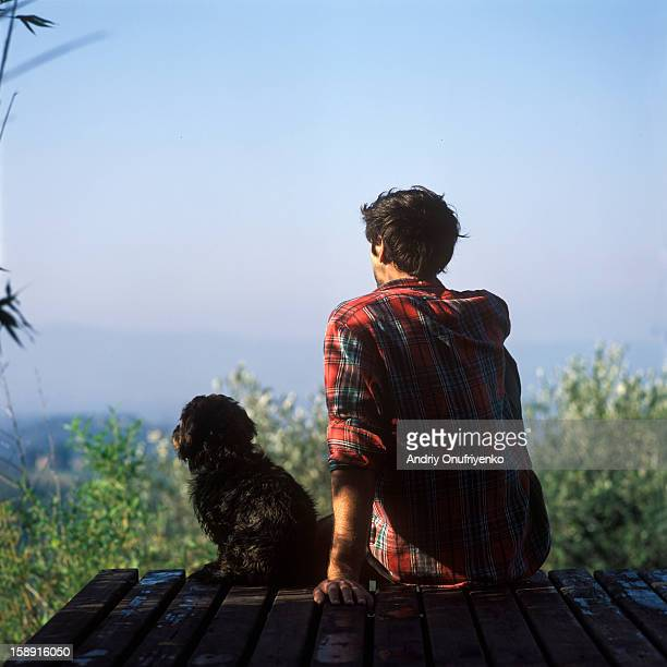 Man sitting on terrace with his dog