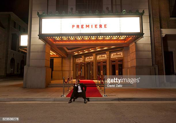 Man sitting on the curb of the red carpet
