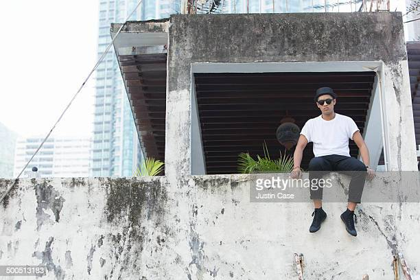 man sitting on the edge of a balcony