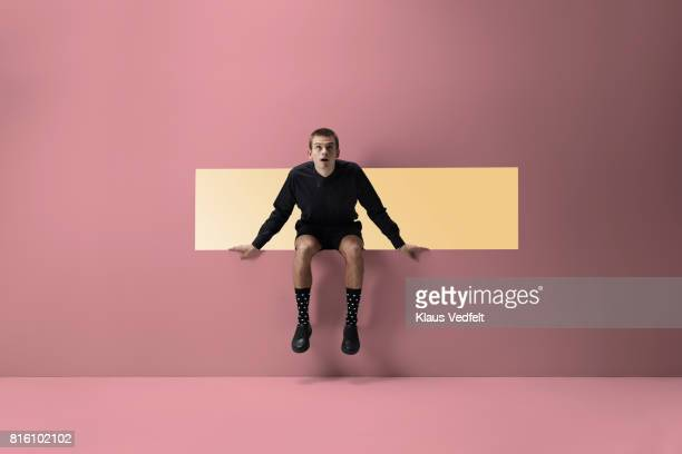 Man sitting on the edge of rectangular opening in coloured wall
