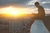 Risky man sitting on the edge of the roof with smartphone and listening music