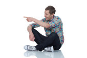 Man sitting on the floor and pointing
