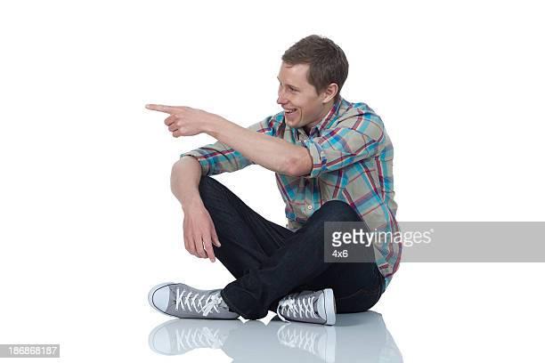 床に座って男と指を指す