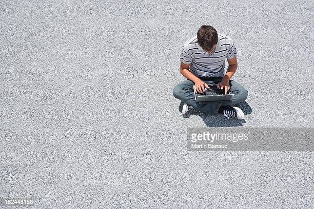 Man sitting on the ground working on his laptop computer
