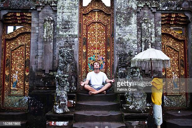 A man sitting on the steps of a temple meditates with a foggy background in Bali, Indonesia.