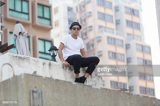 man sitting on the top of a building among the sky