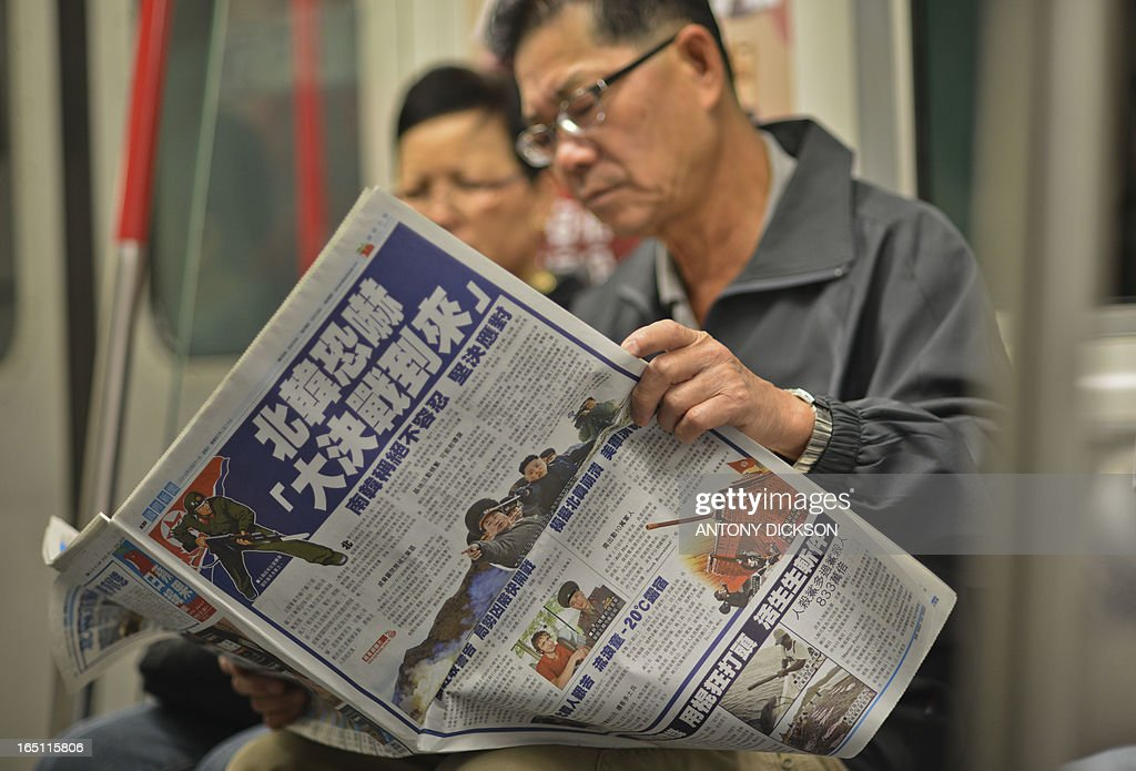 A man sitting on the underground in Hong Kong reads a Chinese language newspaper leading with reports on the recent North Korean military developments on March 31, 2013. North Korea on March 30 declared it was in a 'state of war' with South Korea and warned Seoul and Washington that any provocation would swiftly escalate into an all-out nuclear conflict. China, North Korea's sole major ally and biggest trading partner, appealed for 'joint efforts' to reduce tensions on the Korean peninsula on March 29. AFP PHOTO / Antony DICKSON